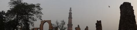 Panorama of Qutb Minar standing tall against the ruins
